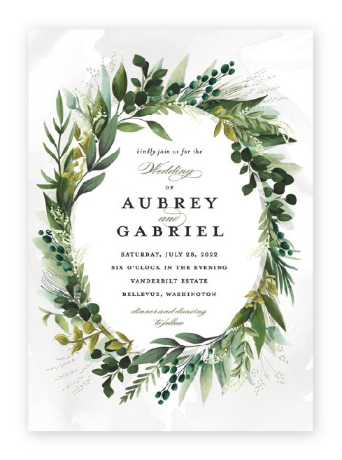Wedding invitation featuring a lush frame of green leaves around classic script and serif wording.