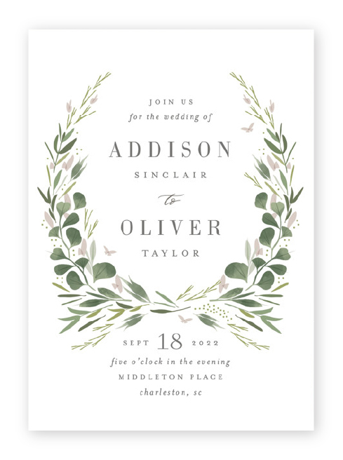 A partial wreath of green botanical and soft pink floral elements frames the names, with wedding details below in these invitations from Minted.
