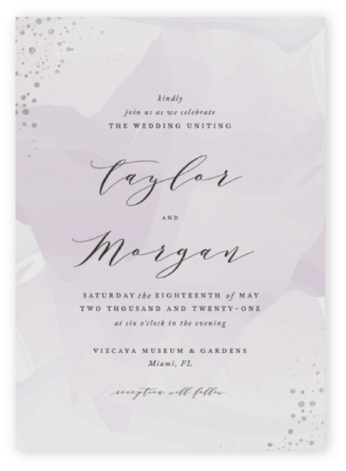 These purple and silver wedding invitations feature black modern script and serif text on an abstract, soft lilac watercolor background with dots of silver foil at the corners.
